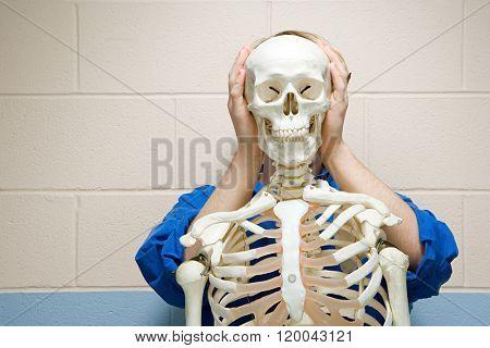 Male student stood behind human skeleton