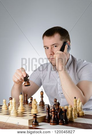 Man Holding A Phone In Their Hands And Playing Chess