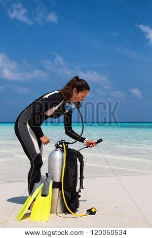 Female scuba diver checking her oxygen tank