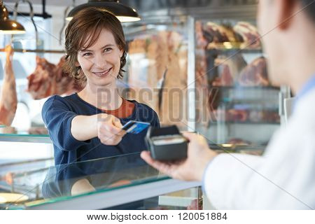 Female Customer Paying In Butchers Shop Using Credit Card