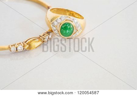 Closeup Green Jade Ring And Gold Bracelets On Blurred Gray Marble Stone Floor Background
