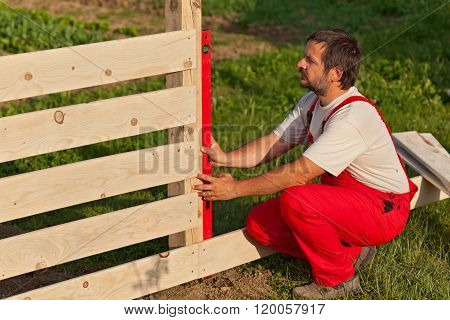 Man Building Wooden Fence