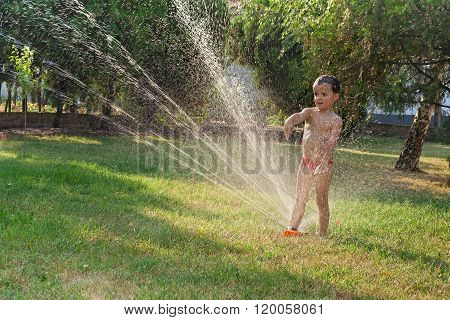 Little Boy Playing With The Garden Sprinkler