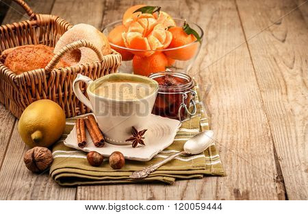 Cappuccino coffee in cup and fruits for breakfast. Tangerines sweet jam on wooden board rustic style