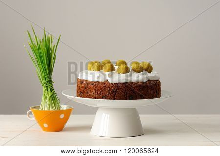 Simnel, English Easter Cake In White Stand And Bright Green Grass On White Table