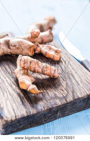 Garden Fresh Tumeric Spice Root On Wooden Board