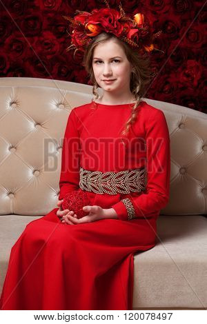 Portrait Of A Little Girl In A Flower Wreath And Red Dress Sitting On The Couch