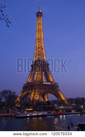 PARIS - MARCH 17: Eiffel Tower illuminated and the bridge Passerelle Debilly view from the Seine qua