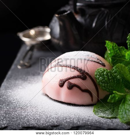 Individual mousse cake in the form of hemisphere covered with pink glaze with mint leaves on dark background. Holiday food concept. ** Note: Shallow depth of field