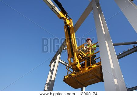 Steel worker operating cherry picker