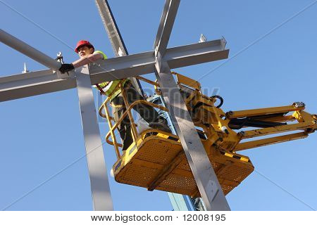 Steel worker on cherry-picker