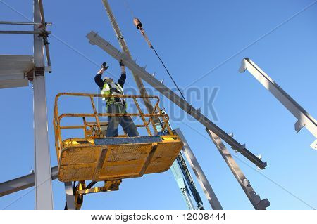 Steel worker on cherry picker.