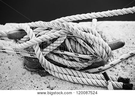 Nautical ropes tied around horn cleat on dock, close up in black and white. Key West harbor, Florida.