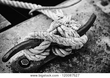 Nautical rope tied around horn cleat on dock, close up in black and white. Key West harbor, Florida.