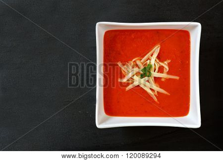 Red pepper soup in a square bowl on slate