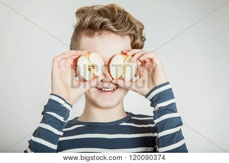 Child Holding Apple Halves In Front Of His Eyes