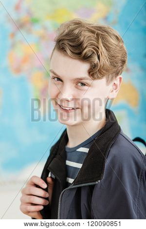 Smiling Boy Standing In Classroom Holding Knapsack