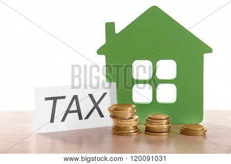 House figure, coins and tax sign, closeup