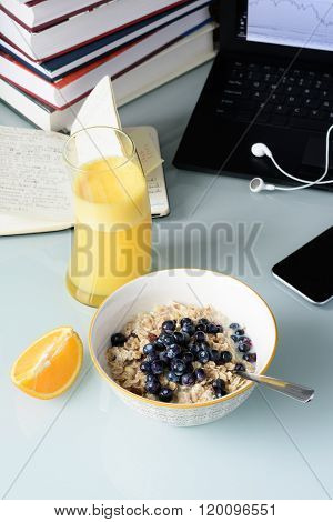Healthy breakfast, muesli with berries and orange juice, laptop, phone and books.