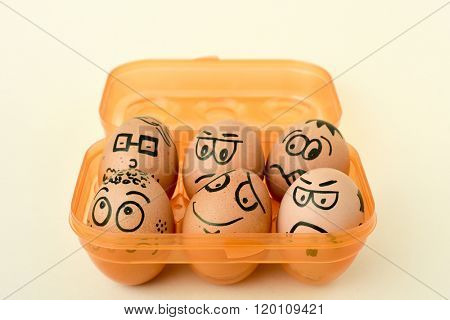 a pile of brown eggs ornamented with funny faces in an orange egg box, on an off-white background