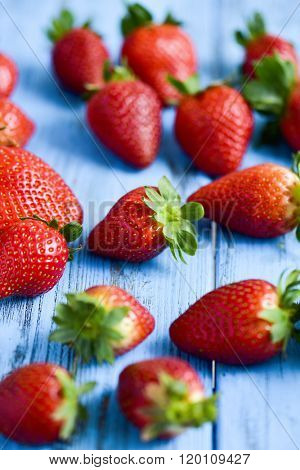 closeup of a pile of appetizing strawberries on a blue rustic wooden surface