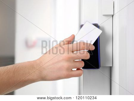 Security alarm keypad with male hand and card, closeup