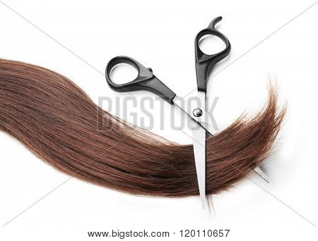 Hairdresser's scissors with strand of dark brown hair, isolated on white