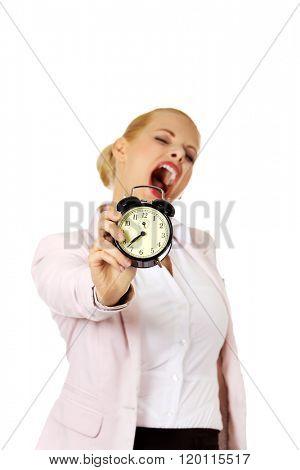 Yawning business woman holding alarm clock