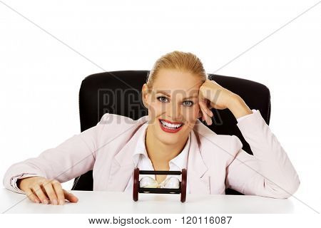 Happy business woman sitting behind the desk with sandglass