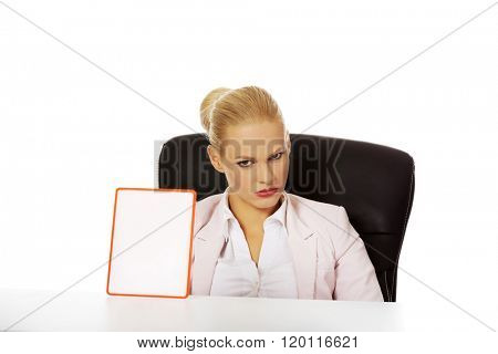 Serious business woman sitting behind the desk and holding board with ban