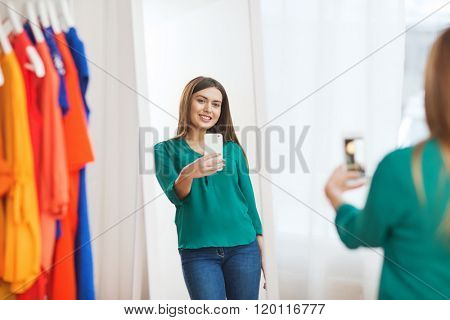 clothing, fashion, style, technology and people concept - happy woman with smartphone taking mirror selfie at home wardrobe
