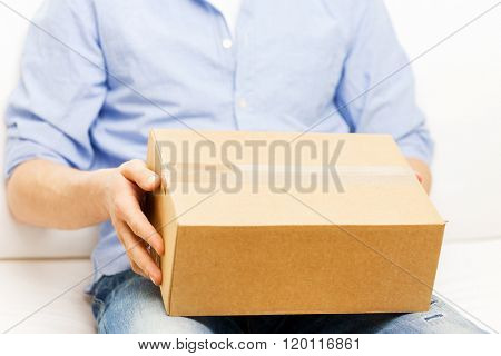 delivery, mail and people concept - close up of man with cardboard box or parcel at home