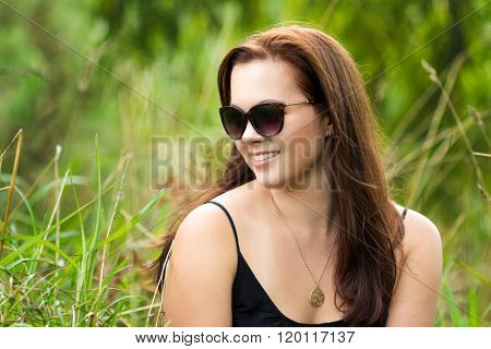 Woman sitting in green grass