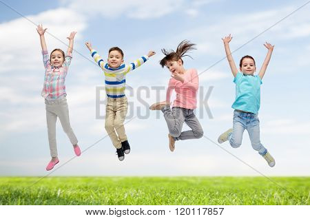 happiness, childhood, freedom, movement and people concept - happy little children jumping in air over blue sky and grass background