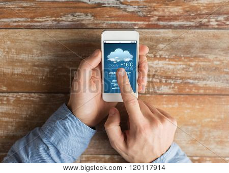 people, weather cast and technology concept - close up of male hands holding smartphone with forecast on screen