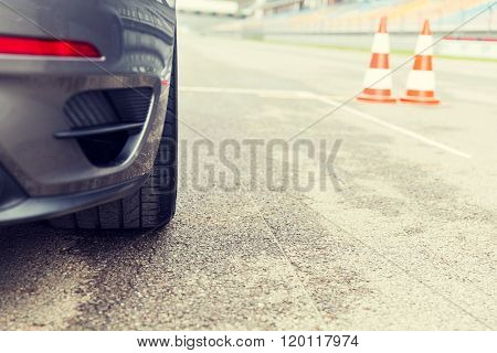 racing, motosports, extreme and motoring concept - close up of sports car front on speedway of stadium