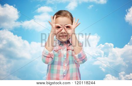childhood, fun, gesture and people concept - happy little girl making faces over blue sky and clouds background