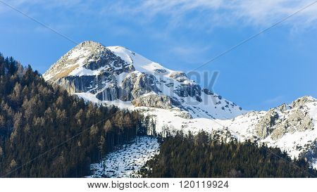 Panoramic View Of Idyllic Winter Wonderland With Mountain Tops In The Alps On A Sunny Day With Blue