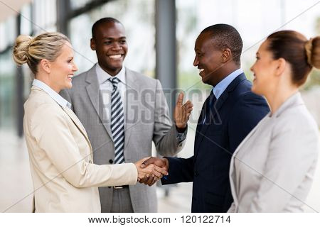 happy african man introducing businesswoman to business partners