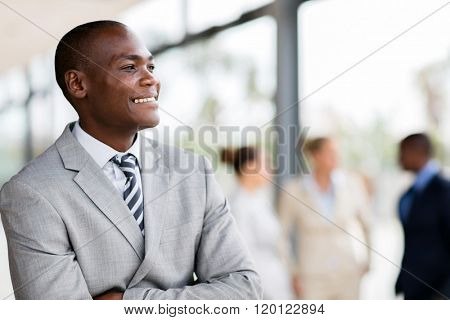 young african male corporate worker daydreaming in office