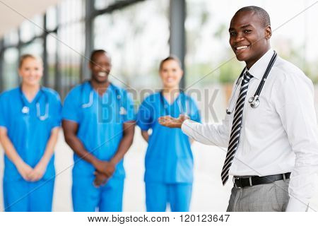 happy african doctor presenting medical team