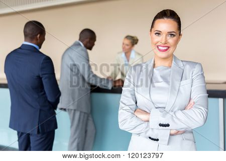 happy young businesswoman standing at hotel reception