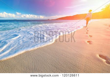 Woman at beautiful beach at Seychelles walking on sand. Focus on footprints.