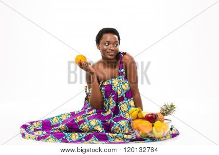 Cute lovely pensive african american young woman in colorful sundress sitting and holding orange over white background