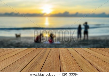 Wood table top on blurred beach and sunrise background for presentation product.