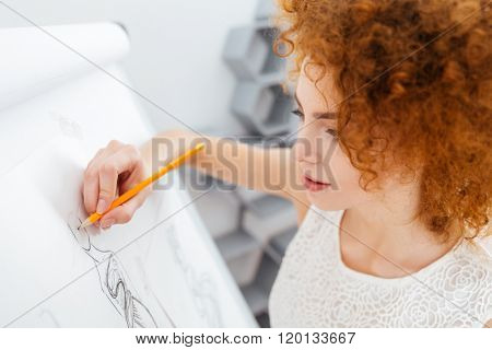 Beautiful curly redhead young woman fashion designer making sketches on flipchart