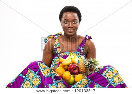 Cheerful beautiful African American young woman in bright sundress sitting and holding different exotic fruits over white background