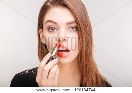 Beauty portrait of pretty young woman doing makeup with red lipstick over white background