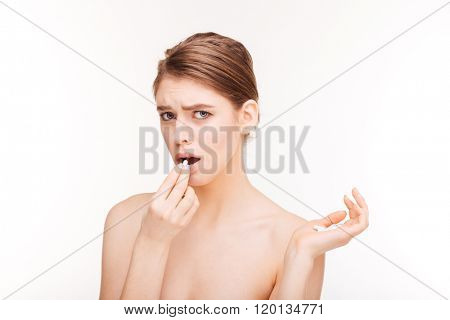 Sad woman holding pill isolated on a white background
