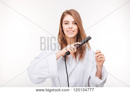 Beautiful happy young woman in bathrobe using hair straightener over white background
